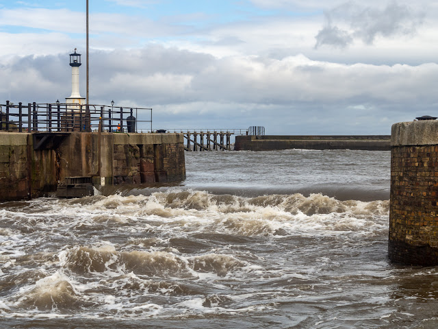 Photo of water creating waves in Maryport Marina as it pours over the closed sea gate