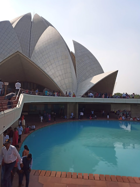 View of Lotus temple and one of its adjacent pools, with people sitting around the water