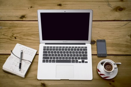 um notebook, café e um  caderno