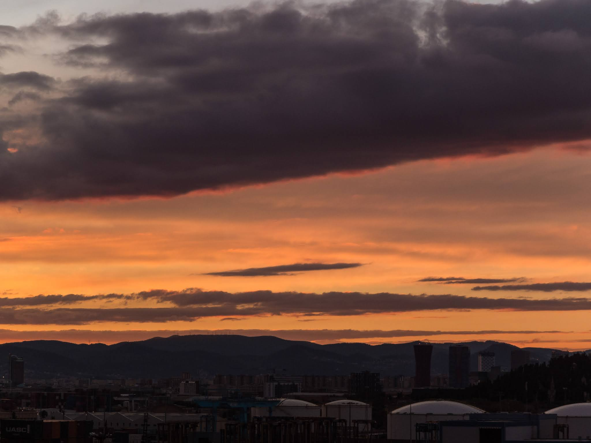 Sunset view from the port of Barcelona with a mountain range in the background.