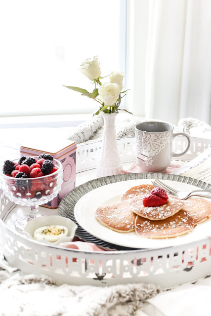 pancakes on vintage tray with berries and a single white flower to celebrate  an intimate valentines day in bed.
