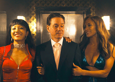 Constance Wu and Jennifer Lopez wrap their arms around Frank Whaley as they walk into a strip club in a movie still for the 2019 film Hustlers
