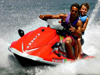Camp counselor and camper jet skiing at Aloha Beach Camp's Castaic Lake summer camp activity site.