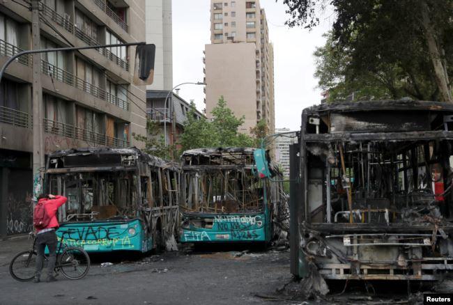 Un hombre toma fotos de autobuses calcinados en Santiago la víspera durante protestas contra el alza de precio de los boletos de metro / REUTERS
