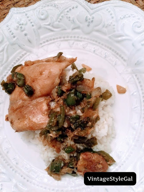 Chicken thighs plated with green pepper and onion over rice