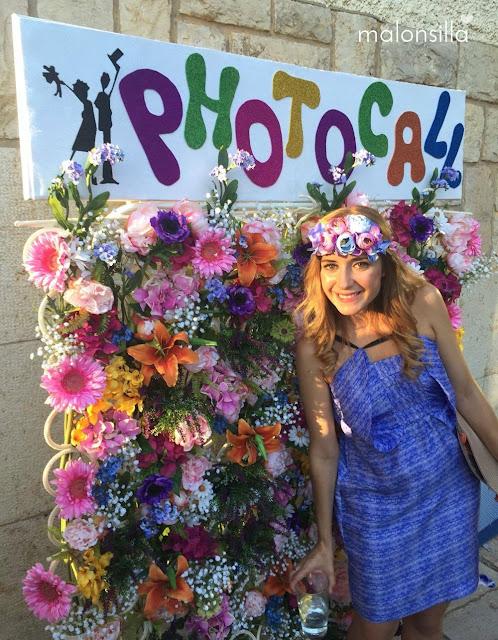 Look invitada boda con vestido corto en azul y malva, diadema de flores y bolso abanico en photocall de boda con flores