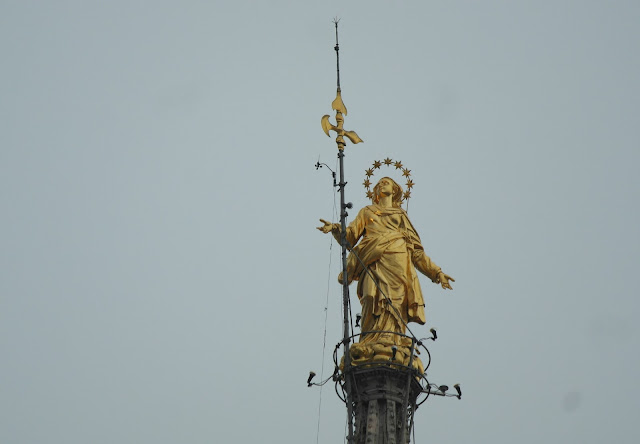 Gold statue rooftop Duomo Cathedral Milan, Italy