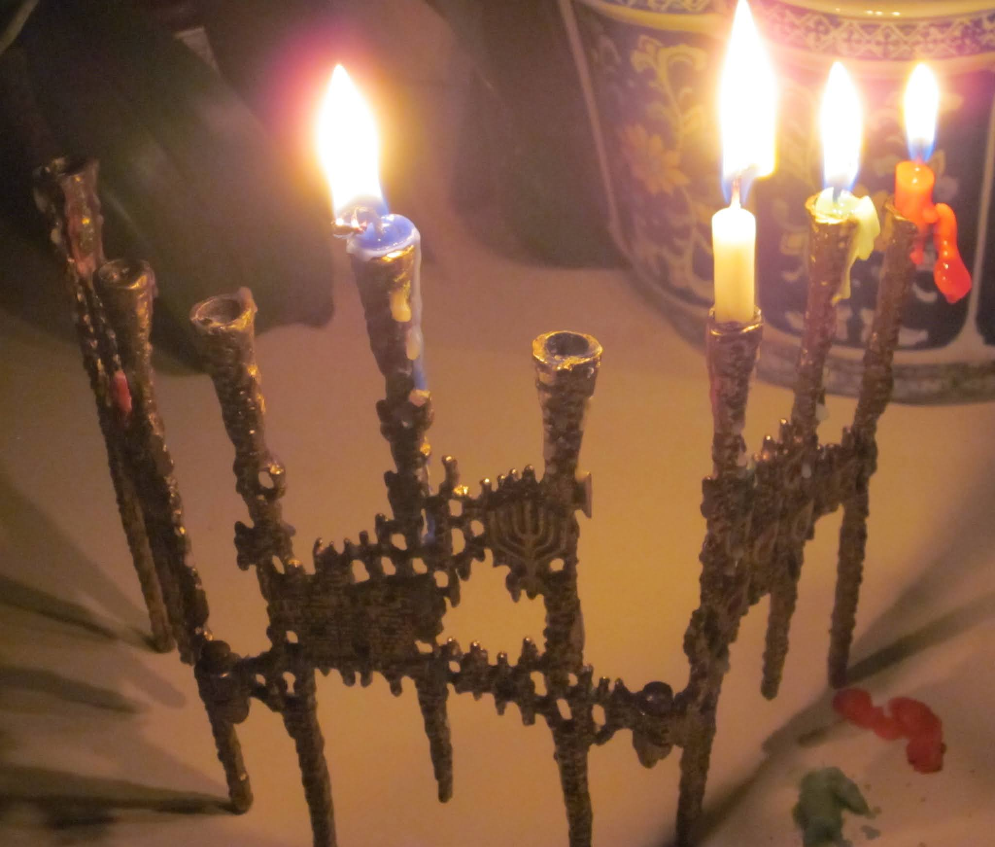 photo of a funky modern Chanukah menorah with shamash, first, second, and third candles lit