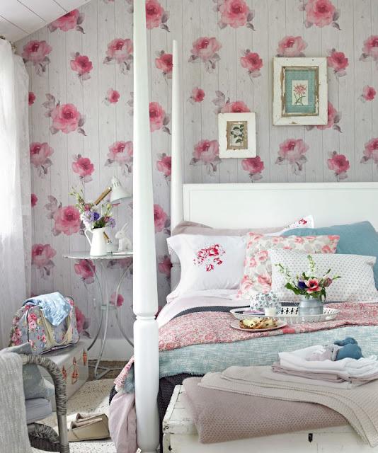 Kamar tidur dengan wallpaper mawar merah muda dan tempat tidur empat poster putih