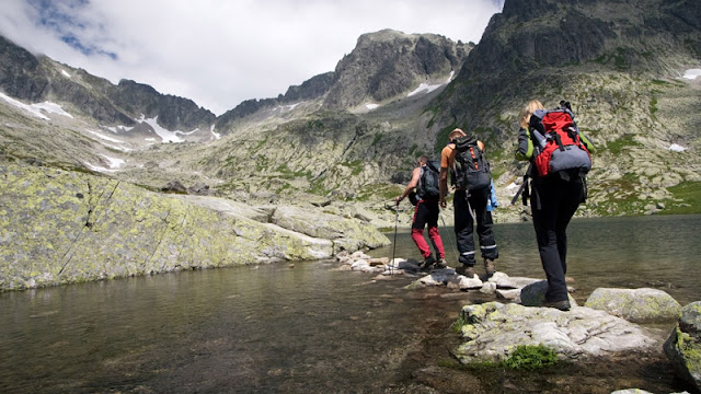 a group of hikers crossing water on top of rocks