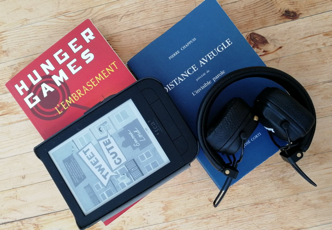 deux livres (hunger games et distance aveugle) posés sur une table, avec une liseuse affichant tweet cute et un casque audio.