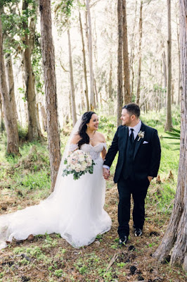 bride and groom smiling in forest