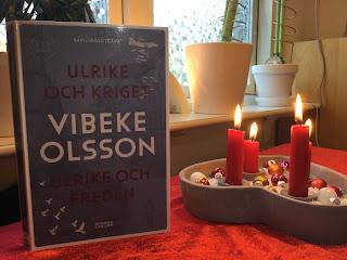 Bild på boken bredvid en tänd adventsljusstake med fyra tända ljus