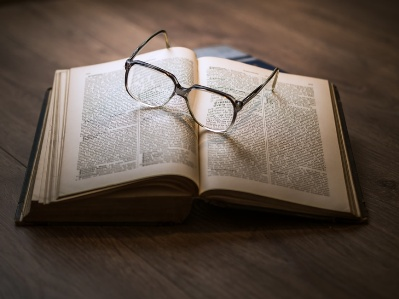 A photo of a pair of open reading glasses on the pages of an open book