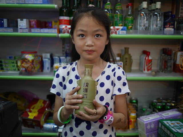 girl holding bottle of 皖酒王