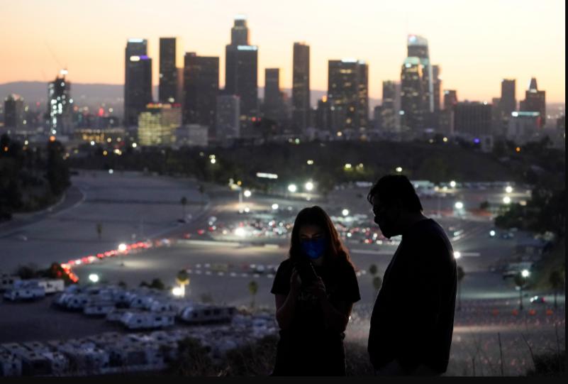 Visitantes con mascarilla observan un sitio de vacunación en el Estadio Dodger, de Los Ángeles, el viernes 15 de enero de 2021 / VOA