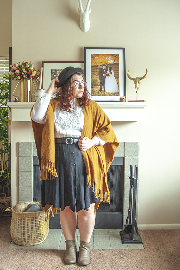 An outfit consisting of a black bowler hat, brown shawl with fringe, white vintage blouse with lace bib and pleat detailing, tucked into a black pleated skirt with black chelsea boots.