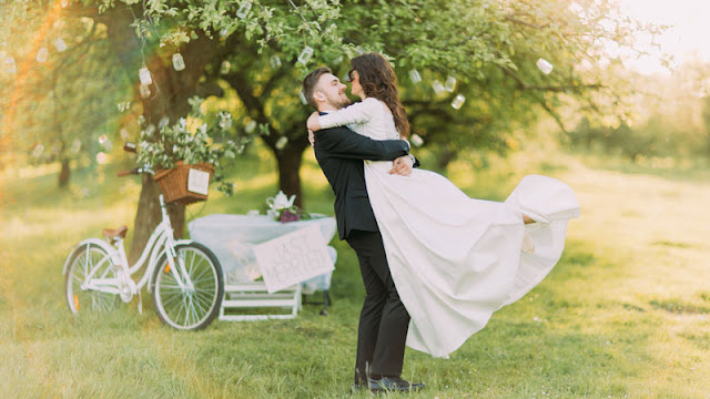 bride and groom embracing beneath tree