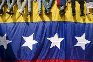 En esta imagen del 26 de octubre de 2016, gente sentada en un muro cubierto por una bandera venezolana durante una protesta contra el presidente Nicolás Maduro en Caracas, Venezuela