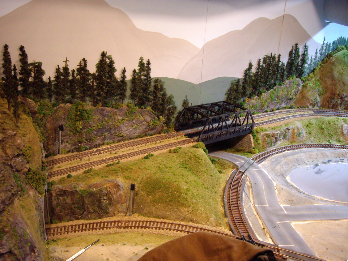 Background terrain and forest scene under construction around an upgraded warren-truss bridge