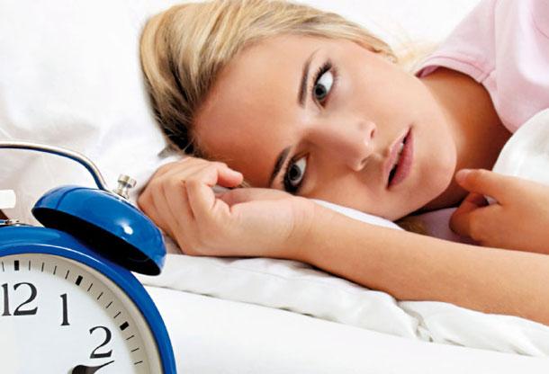 mulher deitada na cama com insonia