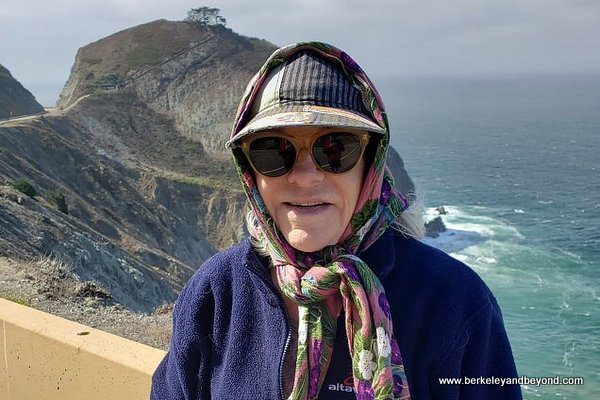 neck scarf holds on lady's hat on scenic stretch on Devil's Slide Trail in Pacifica, California