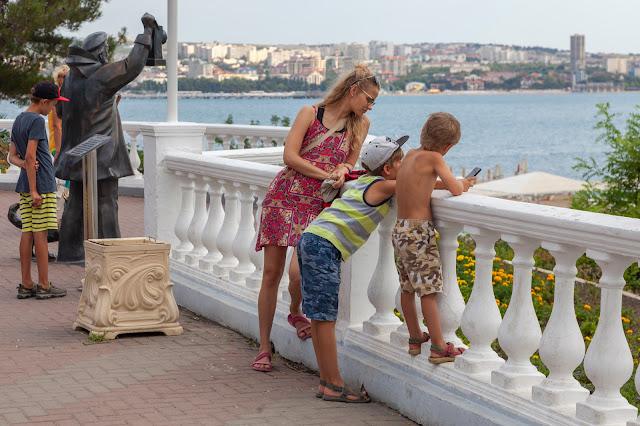 Семья, стоящая на набережной, мальчику интересна скульптура Старый моряк с маяком в Геленджике, Россия
