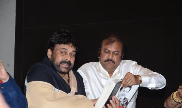 Chiranjeevi and Mohan Babu at the book launch. Mohan Babu helps Chiranjeevi to hold the book. When Legends Meet, Social Media goes Berserk. Chiranjeevi and Mohan Lal.
