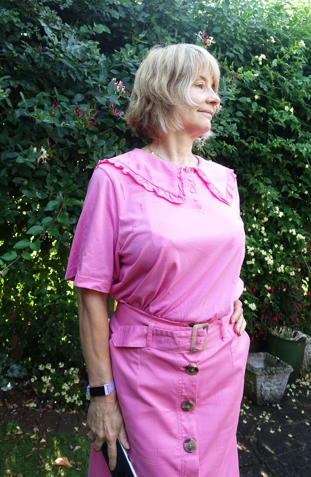 Aging gracefully over 50:  style blog Is This Mutton blogger in pink top with statement collar and belted pink skirt with green mules.