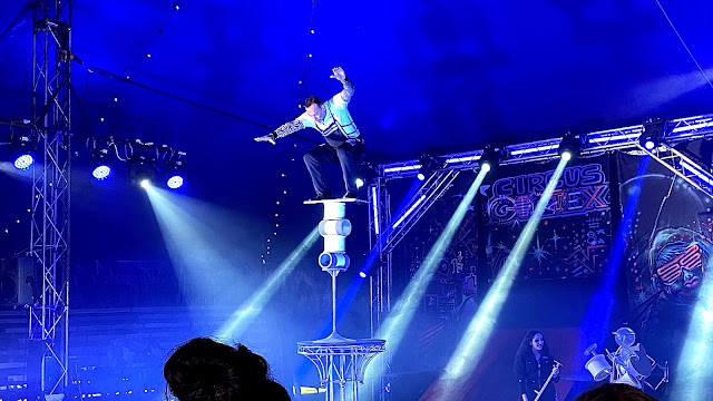A man standing on a pile of props that aren't very stable at the circus