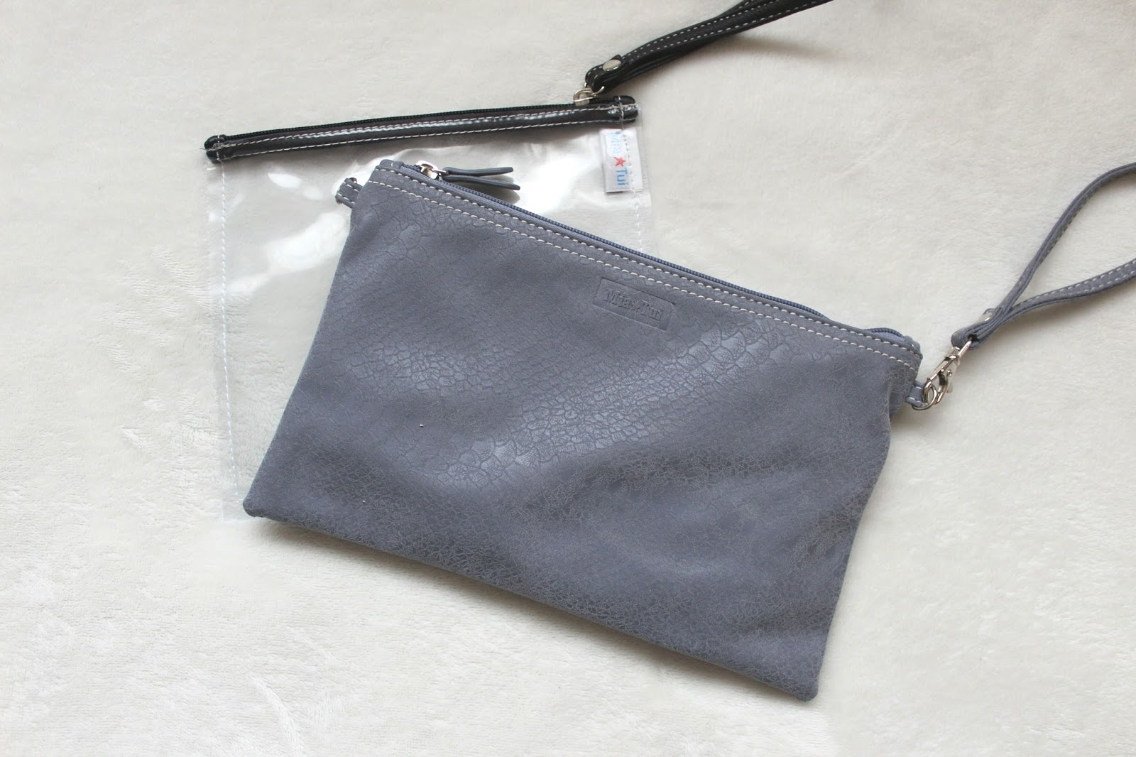 Small clear bag with a small grey clutch bag laid on top.