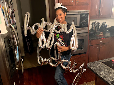 "Black woman holds ""Happy"" and ""B-Day"" balloons"