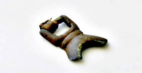 Fragmento recuperado de una hebilla de bronce de la cultura Thule que aún conserva parte de su correa de cuero.
