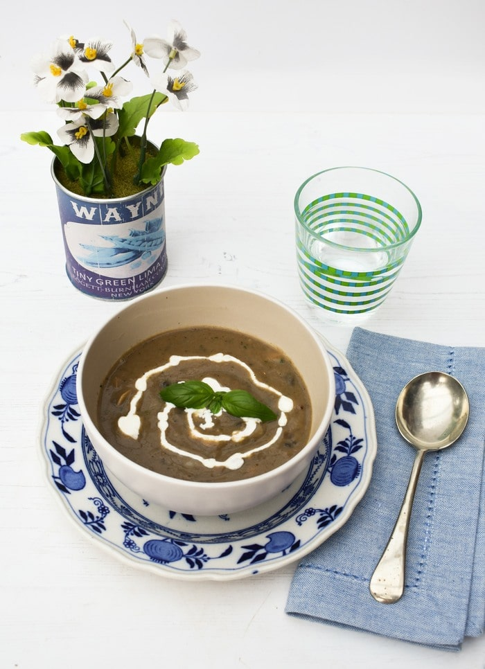Table set up of bowl of mushroom soup sitting on a blue & white floral plate with a pale blue linen napkin and beyond the bowl a small pot of violas & a glass of water