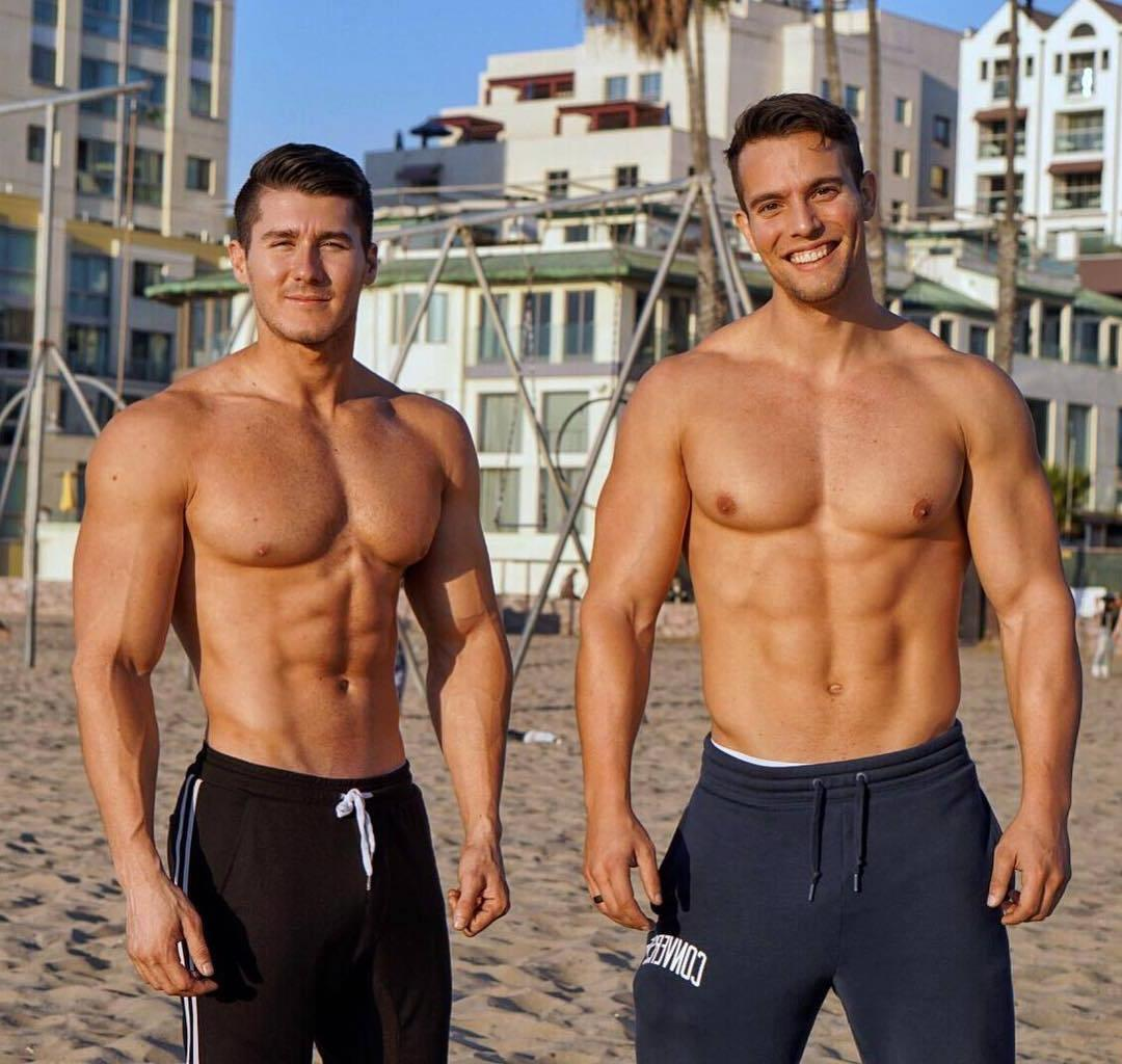 two-muscle-beefy-shirtless-beach-bros-smiling-sand-huge-arms-pecs
