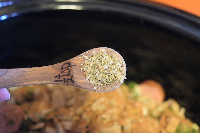 Oregano being added to the crockpot.