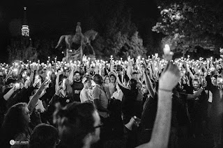 Black and white image of people holding up candles and lit cell phones at a vigil at the Lee statue in Charlottesville Virginia. Photo by Eze Amos