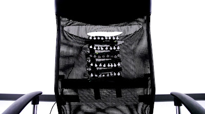 "photo of haptic chair that is connected to a webcam. Facial expressions of the person sitting across are ""Drawn"" in the form of vibrations on the back of the chair."