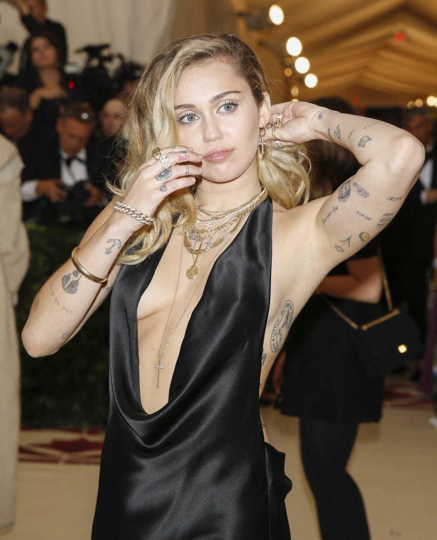 Miley Cyrus posando en una gala enseña sus tatuajes pequeños