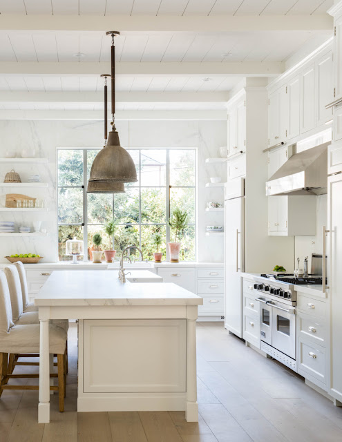 Modern farmhouse white kitchen with steel windows, marble island, vintage pendant lights, by Giannetti Home