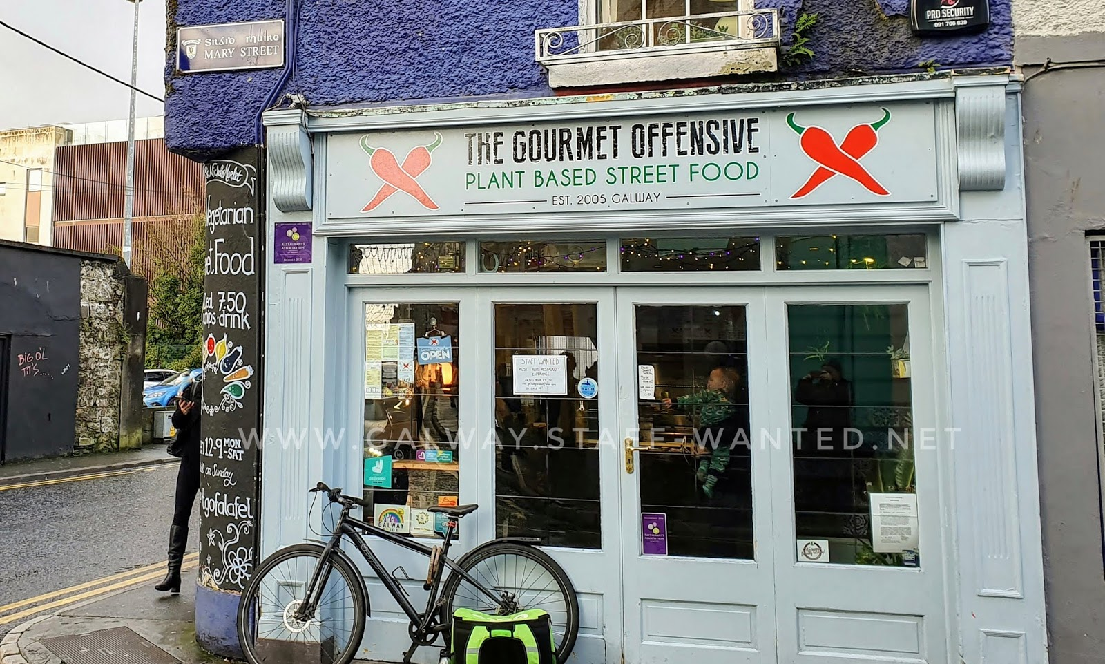 Restaurant shopfront and door, with job advertisement sign on the window and a Deliveroo rider's bicycle dumped immediately outside the door while the rider collects an order.