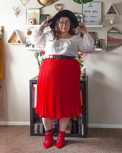 An outfit consisting of a black wide brim floppy hat, a white linen square neck blouse with bishop sleeves tucked into a red pleated midi skirt and red ankle boots.