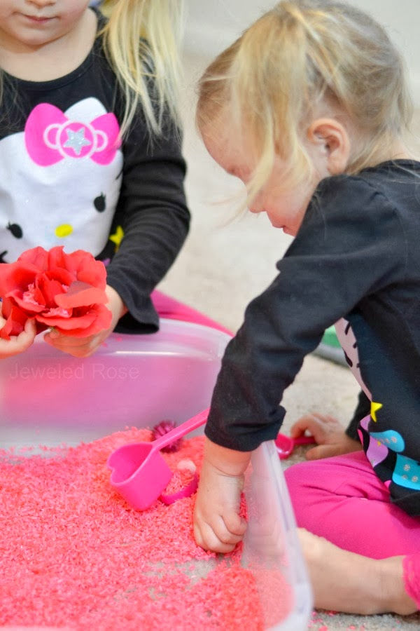 Review a variety of early learning concepts with this easy to make rice play bin, perfect for Valentine's Day! #dyedrice #sensoryactivities #sensorybins #valentinesday #howtodyerice #growingajeweledrose #activitiesforkids