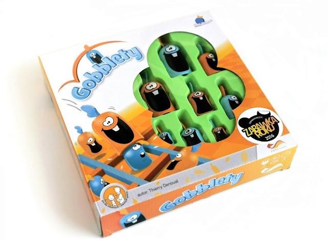 na zdjęciu opakowanie gry gobblety z przezroczystym okienkiem na froncie, przez które widać kilka elementów w postaci pionków, tytułowych gobbletów