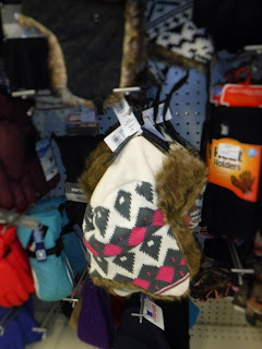 warm winter hats from Bomgaars, including one with a white, pink, and gray geometric pattern and ear flaps
