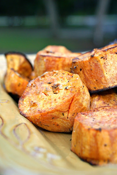 Close up side view of garlic and herb roasted sweet potatoes on a yellow plate.