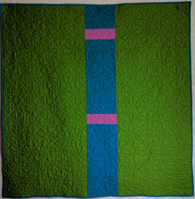 Green quilt back has a wide column of turquoise cut by two narrow strips of violet runs across the center.