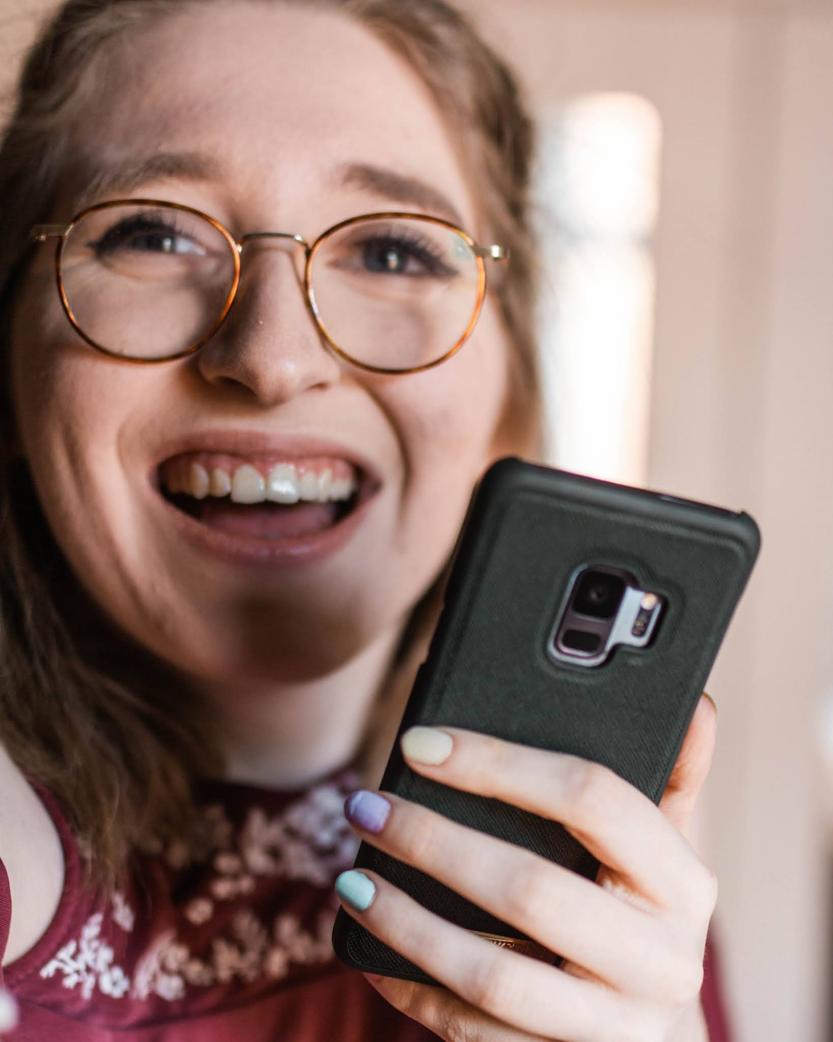 girl smiling and holding phone