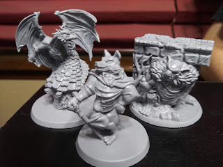 Three of the monster minis. One is the dragon, standing on top of one of the pigs' houses with his wings spread wide. Another is the big bad wolf, standing with a cane propping him up. The third is the bridge troll, hunkered underneath a segment of a bridge.