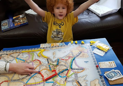 Boy cheering after winning a board game Ticket To Ride